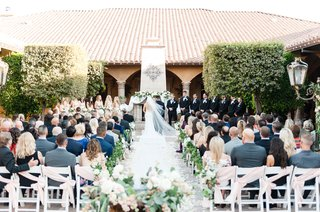 bride-and-groom-at-end-of-aisle-fireplace-mantel-altar-with-greenery-along-aisle-wedding-flowers