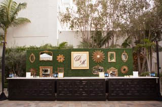 green-hedge-with-gallery-wall-and-initial-frame-behind-wedding-bar