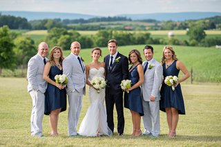 bride-in-a-berta-bridal-gown-and-groom-in-a-navy-blue-ralph-lauren-tuxedo-with-bridal-attendants