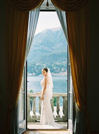 bride-on-balcony-in-bridal-suite-lake-como-views-veil-hair-up-willowby-by-watters-gown
