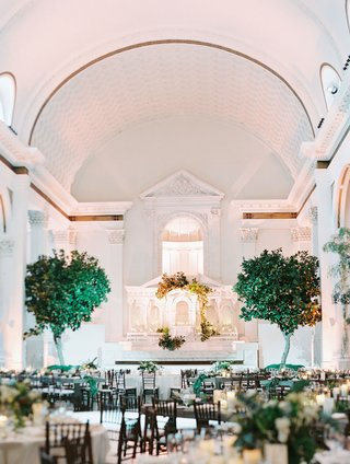 wedding-reception-at-vibiana-downtown-los-angeles-venue-trees-framing-altar-low-centerpieces-white