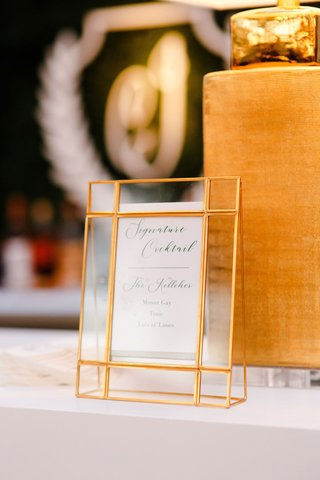 wedding-reception-signature-cocktail-menu-in-gold-glass-frame-at-bar-monogram-hedge-wall