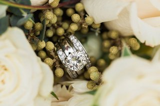 round-stone-engagement-ring-with-a-pair-of-diamond-wedding-rings-in-the-middle-of-white-roses