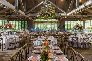 wedding-reception-wood-beams-twinkle-lights-flower-chandelier-pink-orange-flowers-wood-chairs