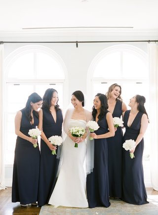 bridesmaids-in-dark-navy-blue-plunging-v-neck-gowns-white-tulip-bouquets