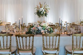 wedding-reception-gold-chair-white-cushion-high-low-centerpiece-taper-candles-drapery