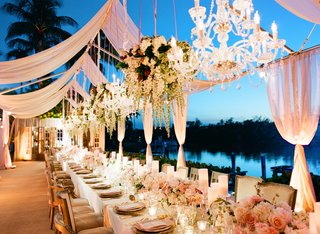 waterfront-wedding-reception-with-sheer-pink-panels-chandeliers-and-floral-arrangements