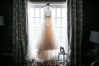 monique-lhuillier-wedding-dress-on-hanger-with-shoes-on-stool