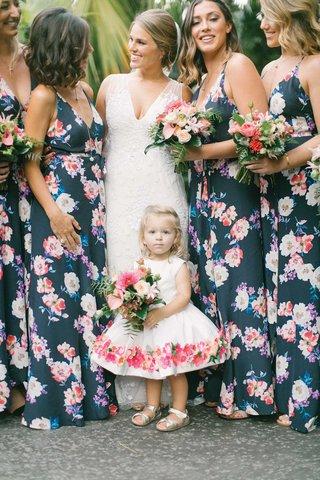 bride-in-v-neck-wedding-dress-bridesmaids-in-navy-floral-bridesmaid-dresses-flower-girl-flower-dress