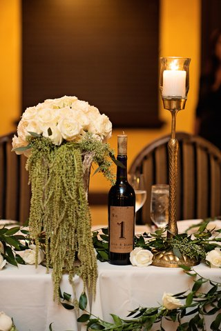 head-wedding-table-with-white-roses-green-amaranthus-greenery-table-number-on-wine-bottle