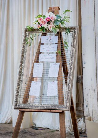rustic-wedding-outside-of-barn-wood-easel-chicken-wire-gold-frame-pink-flowers-greenery