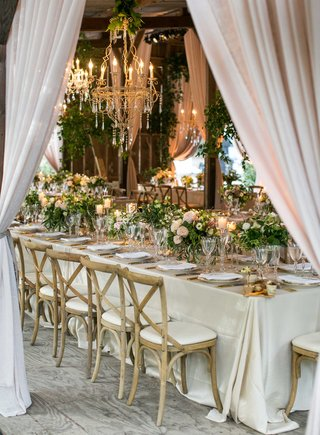 long-reception-table-wedding-wood-chairs-low-centerpieces-greenery-chandelier-drapes