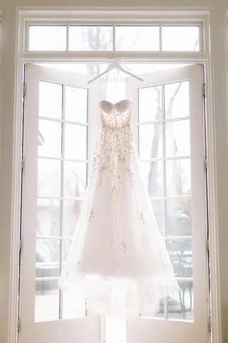 reem-acra-wedding-dress-strapless-personalized-hanger-hanging-in-window-french-doors-sunlight