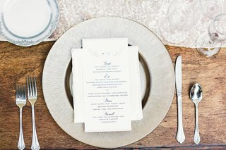 ranch-wedding-reception-wood-table-with-silver-charger-and-reception-program-with-couples-monogram