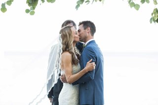 bride-in-pronovias-and-groom-in-ken-baker-kiss-after-being-pronounced-husband-and-wife