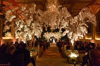 ballroom-wedding-reception-with-tree-branches-and-orchids-down-aisle-and-chuppah-guests