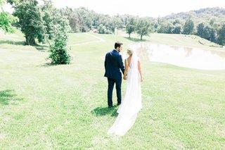 bride-and-groom-walking-through-park-lawn-before-wedding