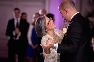 mother-of-the-groom-in-adrianna-papell-gold-sequined-outfit-knit-sweater-dances-with-groom-in-black
