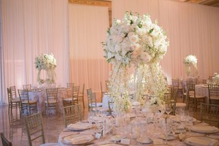 wedding-reception-round-table-with-tall-centerpiece-white-flowers-and-cascading-flowers-to-table