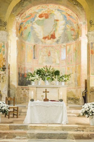 wedding-ceremony-stone-steps-and-altar-fresco-paintings-abbey-chapel-greenery-white-flowers-cross