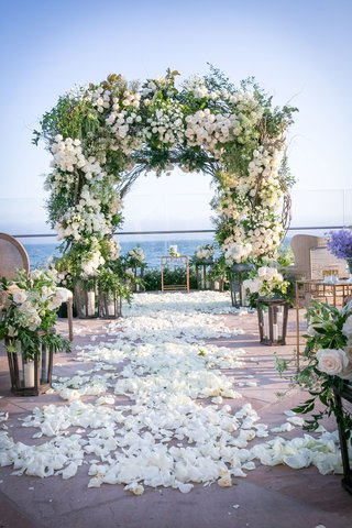 wedding-ceremony-ocean-view-santa-barbara-greenery-white-flower-arch-chuppah-lanterns-flower-petals