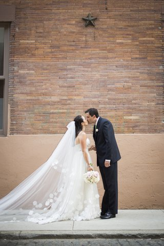bride-and-groom-kiss-in-front-of-brick-wall-in-nyc