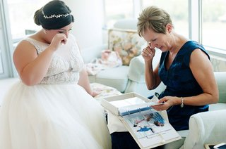 bride-touching-eye-in-touching-moment-between-her-and-her-mom-looking-through-album-photos-proposal