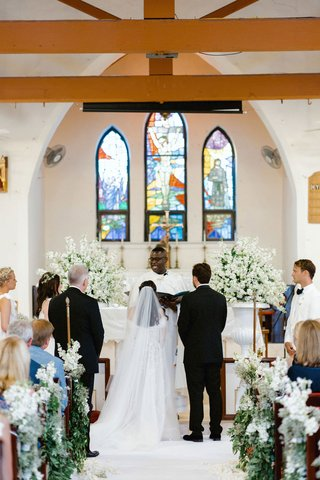 wedding-ceremony-in-little-pink-chapel-harbour-island-bahamas-greenery-white-flowers-altar-pews