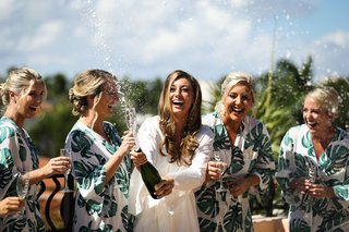 bride-popping-champagne-with-bridesmaids-in-tropical-print-robes-monstera-leaf-design-outside