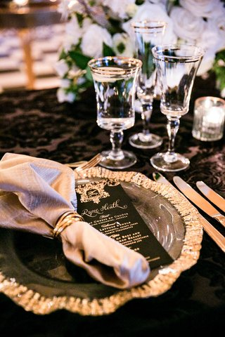 wedding-reception-black-linens-table-gold-rim-glassware-and-charger-black-gold-menu-card-calligraphy