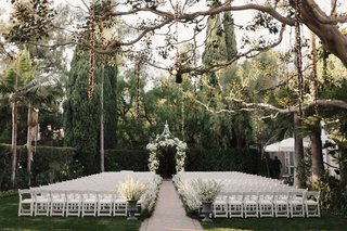 wedding-ceremony-white-chairs-urns-white-flowers-lights-hanging-from-tree-beverly-hills-ceremony