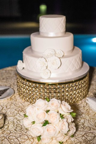 wedding-cake-on-gold-stand-white-sugar-flowers-ribbon-quilted-layer-tier