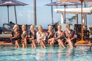bride-bridesmaids-robes-feet-in-pool-drinks-mimosas-wedding-california-la-valencia-hotel-fun