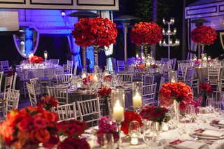 poolside-wedding-with-red-flower-centerpieces-and-purple-lighting