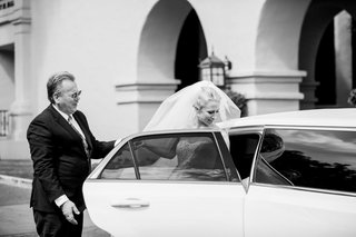 black-and-white-photo-of-bride-getting-into-limo-with-help-from-her-father