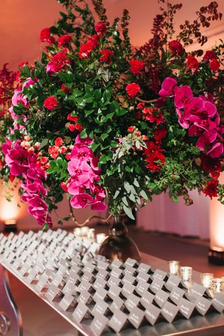 grey-escort-cards-on-table-with-lush-greenery-arrangement-with-red-flowers-and-fuchsia-orchids