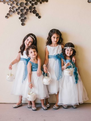 four-flower-girls-carrying-baskets-with-white-dresses-and-blue-sashes-or-bodices-headbands
