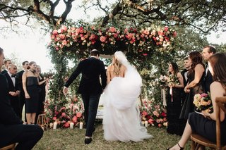 wedding-ceremony-jewish-outdoor-greenery-pink-coral-orange-flowers-guests-in-wood-chairs
