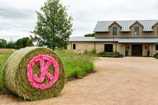 roll-of-hay-with-initials-in-pink-flowers-outside-ranch