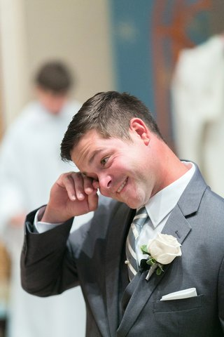 happy-groom-in-grey-suit-grey-white-striped-tie-ivory-rose-boutonniere-wipes-tear-at-altar
