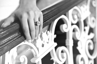 black-and-white-photo-of-brides-hand-on-staircase-railing-with-halo-engagement-ring