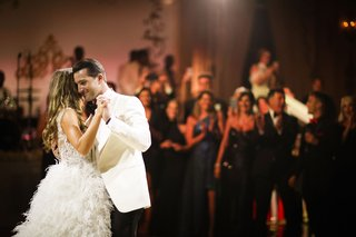 photo-of-bride-in-ostrich-feather-skirt-wedding-dress-groom-in-white-tuxedo-jacket-first-dance