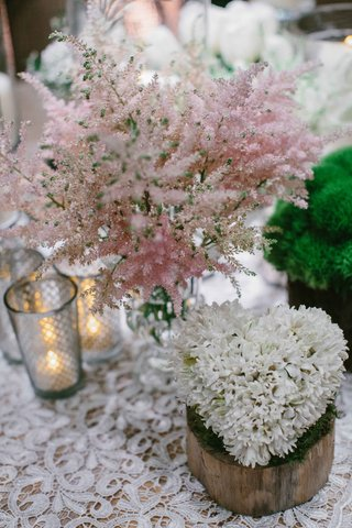 wood-stump-with-white-flower-heart-shape-centerpiece-pink-soft-flowers-on-lace-table-linen
