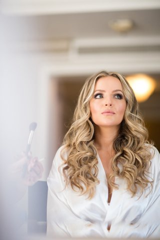 bride-with-softly-curled-blonde-hair-and-makeup-with-dramatic-eyes-getting-makeup-done