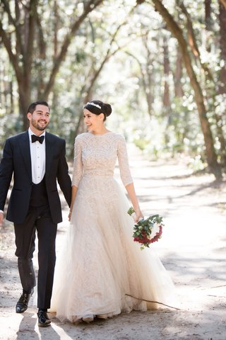 bride-in-long-sleeve-lace-wedding-dress-with-groom-in-tuxedo-walking-through-trees-palmetto-bluff