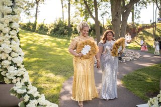 mother-of-bride-and-mother-of-groom-in-gold-and-silver-sequin-gowns-feather-fans-outdoor-ceremony