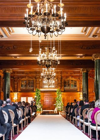 wedding-ceremony-wood-paneling-chandeliers-greenery-arch-white-aisle-runner-wood-round-back-chairs