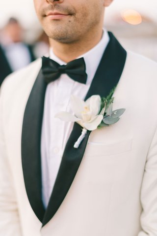 groom-white-white-suit-jacket-black-lapels-boutonniere-orchid-variety-green-leaves-black-bow-tie