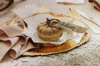 fall-wedding-ideas-gold-pumpkin-with-place-card-ribbon-calligraphy-gold-charger-plate