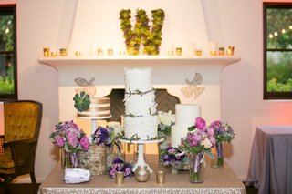 three-wedding-cakes-with-green-and-gold-accents-on-table-with-pink-and-purple-floral-arrangements